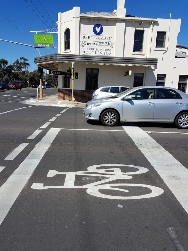 "A ""Forward bike box,"" but only for two of three lanes.  If you want to turn right then mix it with the silver car"